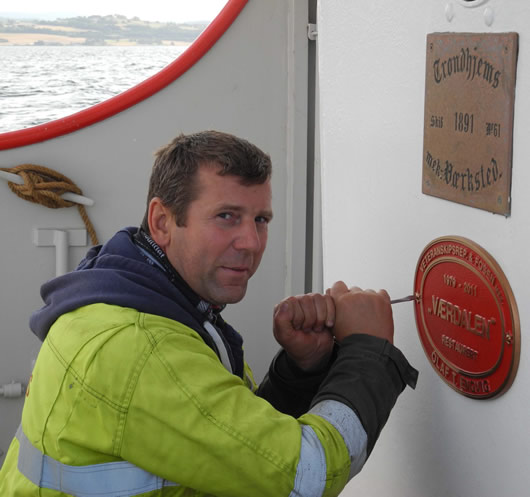 Bosun Algis placing plaque of completion on the restored Vaerdalen.